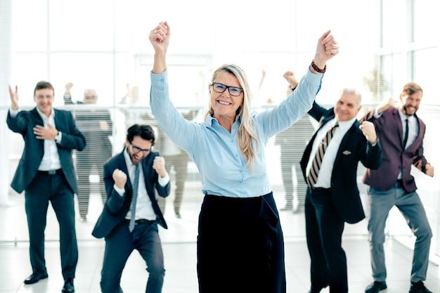 Felice imprenditrice e un gruppo di dipendenti che mostrano il loro successo