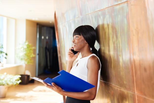 Felice imprenditrice tenendo la cartella con i documenti e parlando al telefono in ufficio