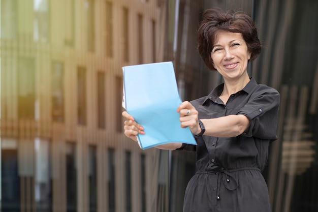 Felice imprenditrice sorridente e in possesso di documenti