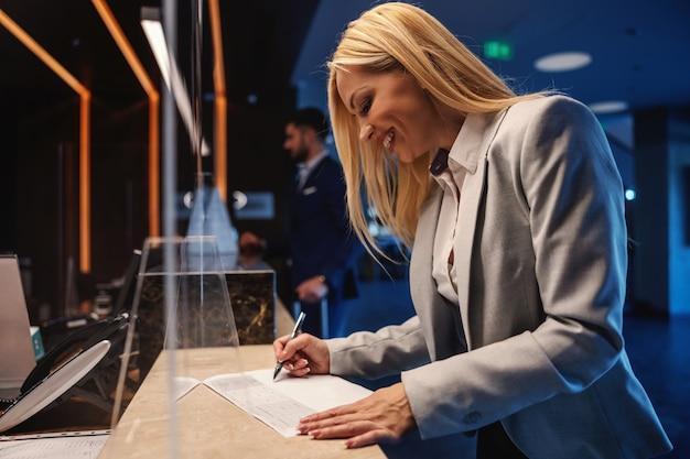 Felice imprenditrice in piedi alla reception e il check-in. sta compilando il modulo. viaggio di lavoro, hotel di lusso, fine settimana