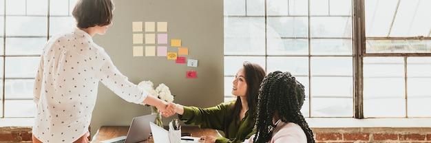 Donne di affari felici che fanno un modello sociale della stretta di mano