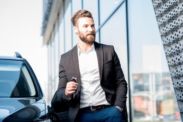 Acquirente felice che tiene le chiavi vicino all'auto di fronte al moderno edificio avtosalon