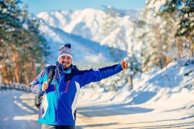 Un campeggiatore felice in inverno in montagna, in piedi sull'autostrada e fermare una macchina