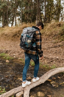 Uomo di campeggio felice nella foresta da dietro il colpo