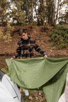 Uomo di campeggio felice nella foresta che fa la tenda