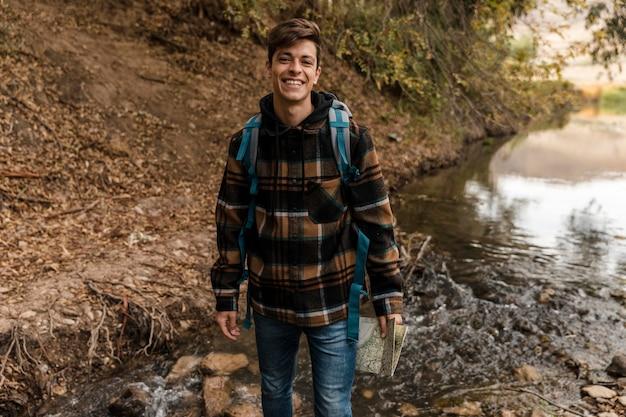 Uomo di campeggio felice nella foresta