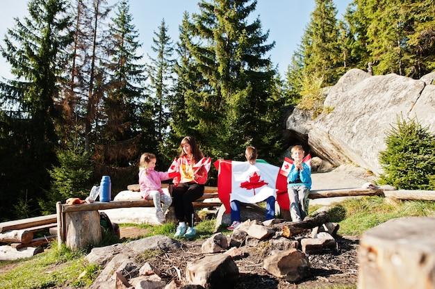 Buona festa del canada. la famiglia della madre con tre bambini tiene una grande celebrazione della bandiera canadese in montagna.