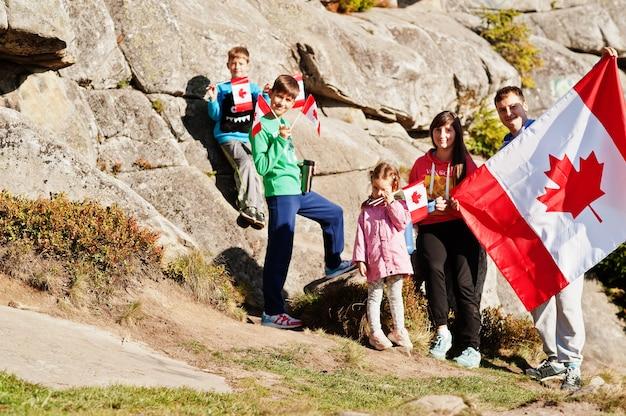 Buona festa del canada. famiglia con la grande celebrazione della bandiera canadese in montagna