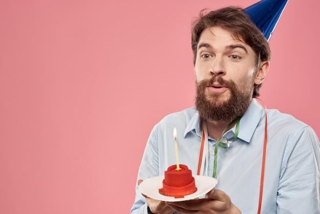 Felice macchina con una torta su una rosa e in un berretto in festa di compleanno