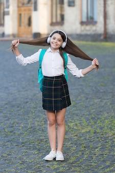 Felice ragazza spensierata torna a scuola ascoltando musica, moderno concetto di adolescente.