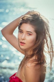 Donna spensierata felice che gode del bellissimo tramonto sulla spiaggia.