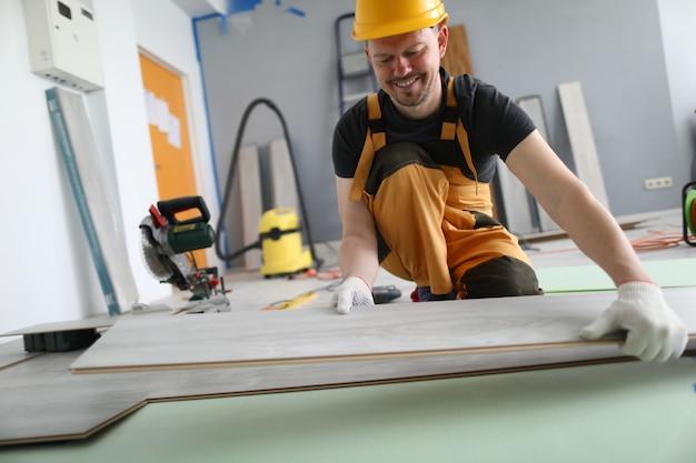 Happy carpenter posiziona i pannelli in laminato sul pavimento