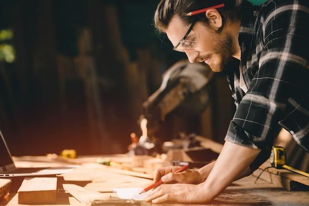 Falegname felice che sorride per disegnare mobili in legno di design nel laboratorio di legno aspetto professionale alta abilità persone che lavorano artigianalmente autentiche