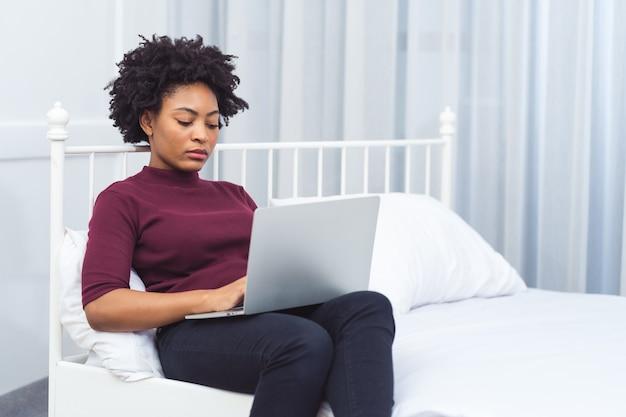 Felice casual bella donna africana americana che lavora al computer portatile mentre si è seduti sul letto in casa.