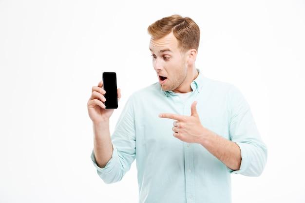 Felice uomo casual che punta il dito sullo schermo dello smartphone sul muro bianco