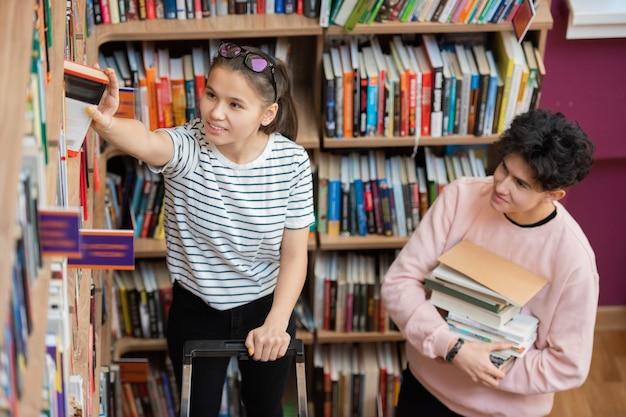 Adolescente casuale felice che prende uno dei libri del suo autore preferito dalla grande libreria nella biblioteca del college con il ragazzo in piedi vicino