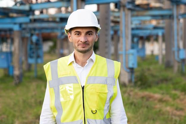 Ingegnere adulto caucasico felice in casco che sorride alla macchina fotografica alla centrale elettrica ad alta tensione all'esterno