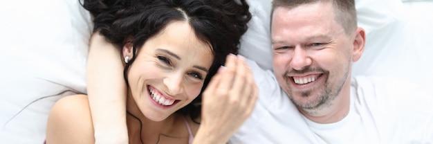 Le coppie beatyful caucasiche felici si trovano sul ritratto di vista superiore del letto. concetto di famiglia sana