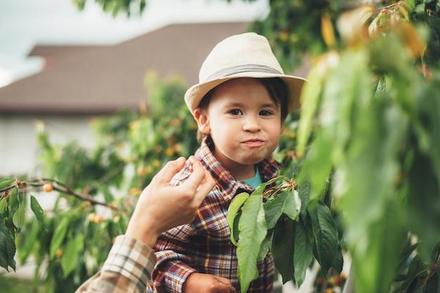 Ragazzo caucasico felice con il cappello che sorride alla macchina fotografica mentre mangia le ciliegie in piedi vicino ai suoi genitori