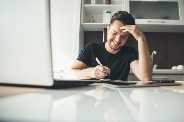 Uomo d'affari caucasico felice che lavora da casa al computer portatile e scrive qualcosa nel libro