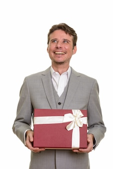 Uomo d'affari caucasico felice che pensa tenendo il contenitore di regalo