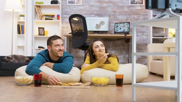 Felice coppia caucasica che mangia pizza seduti sui cuscini per il pavimento guardando la tv mentre il loro gatto si rilassa sullo sfondo.