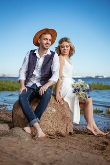 Felice coppia caucasica uomo e donna sulla spiaggia giorno d'estate con in mano un mazzo di fiori