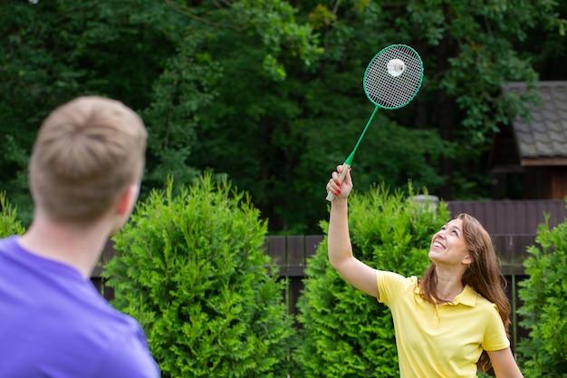 Coppie caucasiche felici giocano a badminton con racchette e volano sulla natura verde. concetto di gioco amatoriale di badminton, attività estive all'aperto