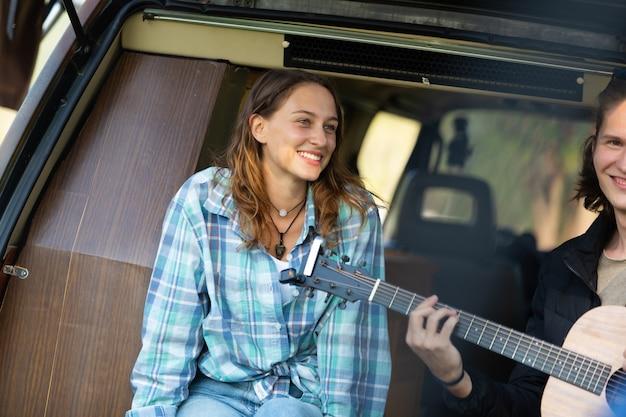 Felice coppia caucasica che suona la chitarra con uno sfondo di auto in tenda