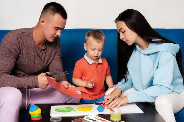 La famiglia caucasica felice è impegnata nel lavoro creativo a casa e si diverte. mamma, figlio e papà scolpiscono con argilla e pittura a tavola
