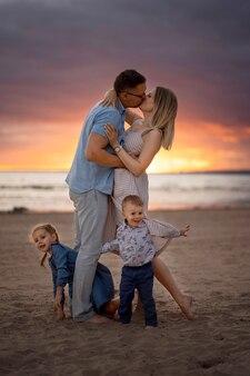 I genitori felici della famiglia caucasica che baciano i bambini si nascondono dietro le loro gambe