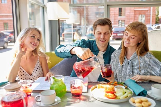 Gli amici caucasici felici stanno riposando nella caffetteria mangiando e divertendosi