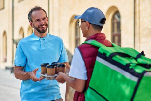 Felice cliente caucasico che riceve quattro tazze di caffè da un corriere maschio con borsa termica