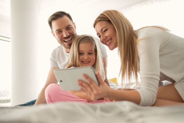 Genitori caucasici felici che ridono mentre guardano lo schermo del tablet con la loro piccola figlia