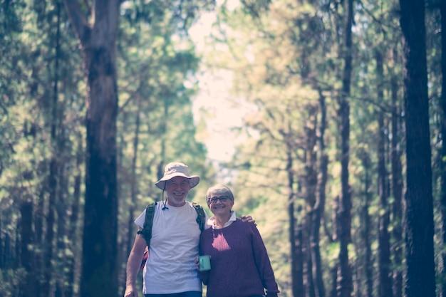 Felice coppia senior caucasica sorride e si gode il viaggio con lo zaino nella foresta naturale all'aperto - concetto di vacanza gratuita alternativa per le persone anziane - stile di vita gioioso e abbraccio e amore