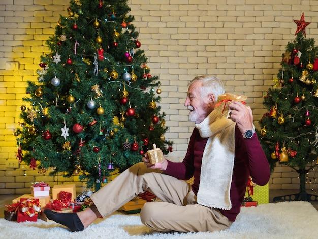 Felice uomo anziano caucasico che tiene il regalo di natale e ascolta cosa c'è dentro mentre è seduto davanti all'albero di natale decorato nel soggiorno