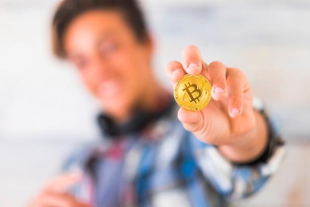 Adolescente caucasico felice che mostra bitcoin - tecnologia del denaro futuro
