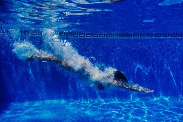 Donna caucasica felice che si tuffa in piscina. vista subacquea. ora legale e concetto di vacanza