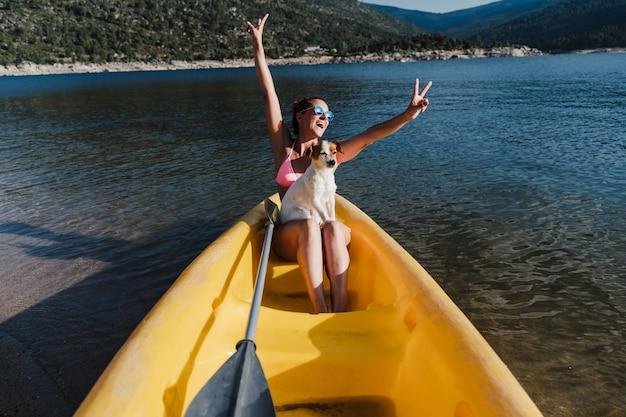 Felice donna caucasica e jack russell dog sitter su canoa gialla nel lago durante la giornata di sole. estate. animali, avventura e natura