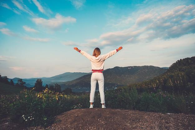 Felice celebrazione del successo vincente donna in abiti bianchi in piedi euforico con le braccia sollevate sopra la testa per celebrare il raggiungimento dell'obiettivo della vetta della montagna durante il viaggio di trekking.
