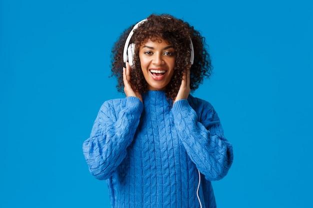 La ragazza sorridente afroamericana carismatica felice ha ottenuto le nuove cuffie del regalo di natale, ascolta musica e gode di battiti fantastici, tocca gli auricolari e guarda la fotocamera, blu