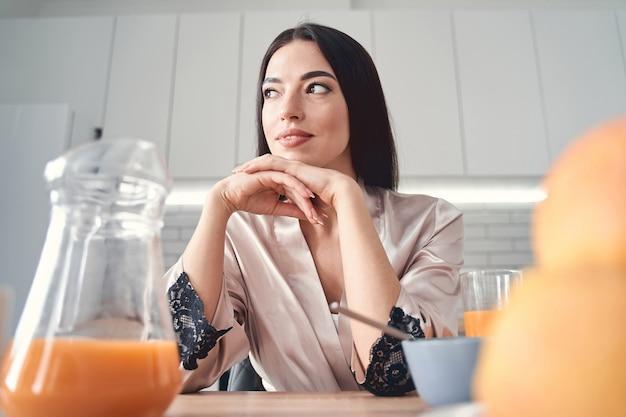 Felice affascinante signora seduta al tavolo della colazione in vestaglia e guardando da parte con un sorriso