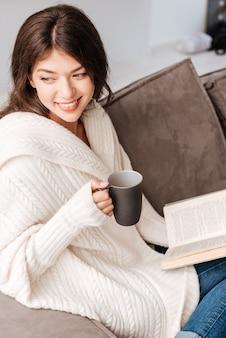 Felice affascinante giovane donna che beve caffè e legge un libro a casa