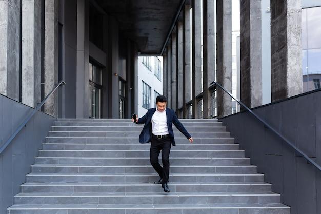 Felice e allegro uomo d'affari asiatico che balla vicino all'ufficio si rallegra della vittoria e del successo