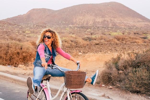 Felice e allegra bella signora bionda riccia che va in bicicletta come una matta ridendo molto