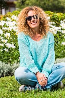 Felice e allegra bella donna adulta caucasica godersi il parco e sorridere alla telecamera con margherita verde naturale in superficie