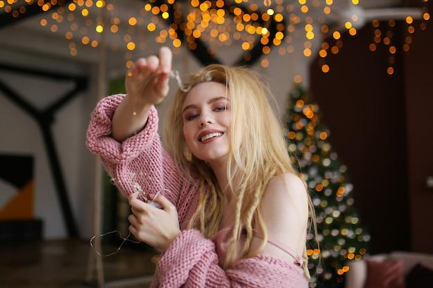 La donna bionda allegra felice celebra il nuovo anno dall'albero di natale