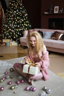 Donna bionda allegra felice che tiene i regali dall'albero di natale