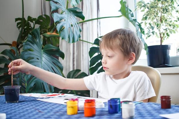 Bambino allegro felice che disegna con la spazzola, nell'interno domestico durante l'autoisolamento e la quarantena del coronavirus. concetto di creatività