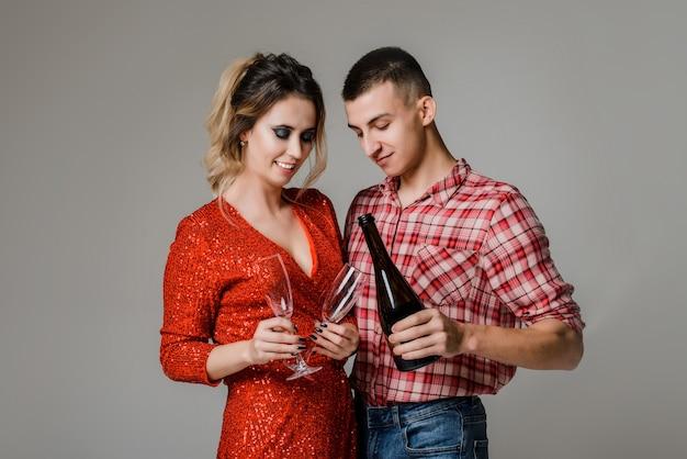 Coppie allegre felici che celebrano il nuovo anno che tengono i vetri con champagne sopra gray